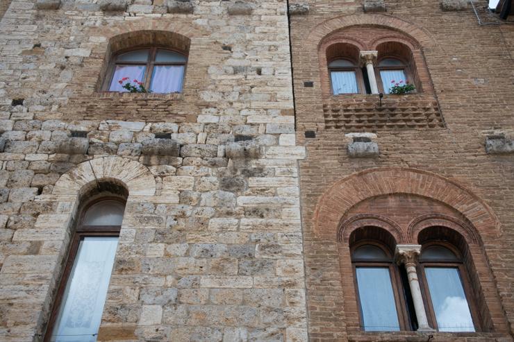 Notar los diferentes detalles arquitectonicos y usos de materiales en los edificios de San Gimignano